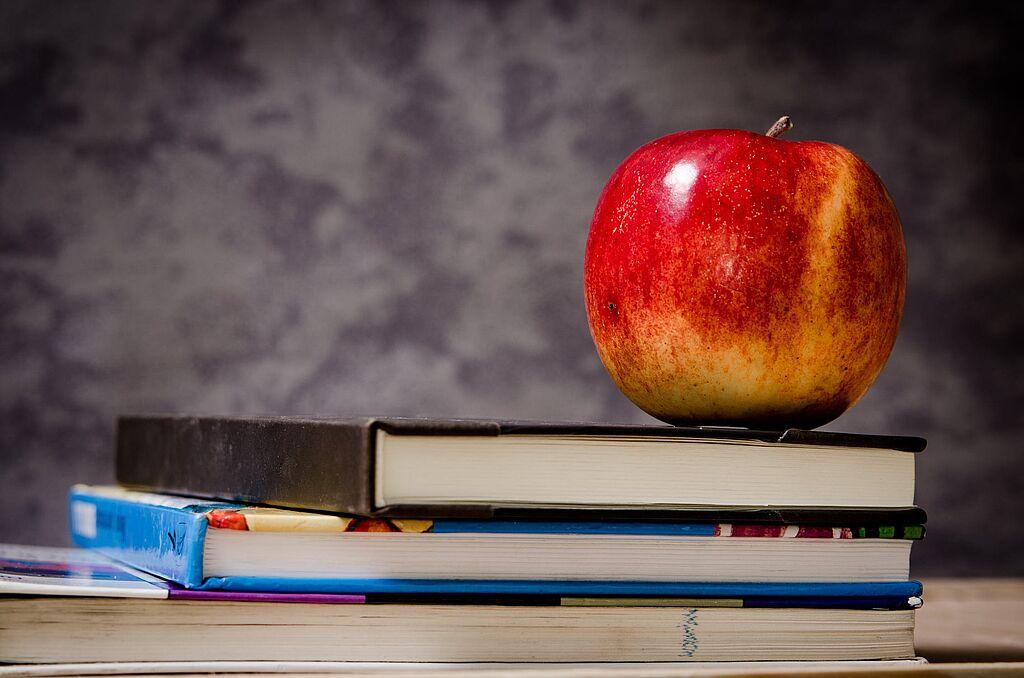 Una mela sopra dei libri