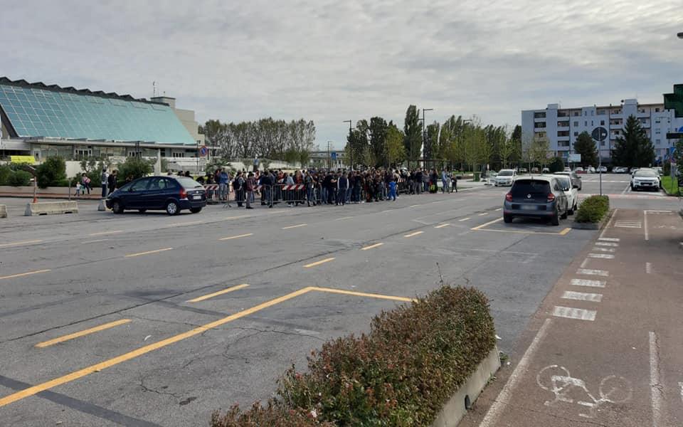 Persone in coda in piazza Aldo Moro per prendere la navetta