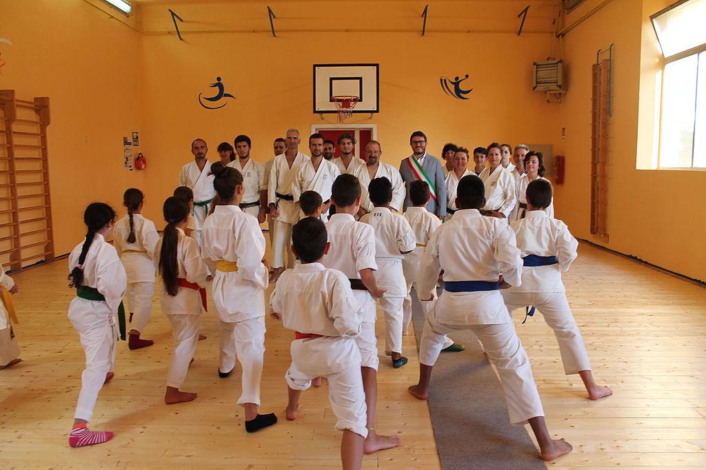 L'assessore Cecchetti con Del Pellegrino e gli atleti che praticano karate all'interno della palestra